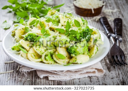 homemade pasta orecchiette with broccoli, Parmesan cheese and basil on a wooden table - stock photo