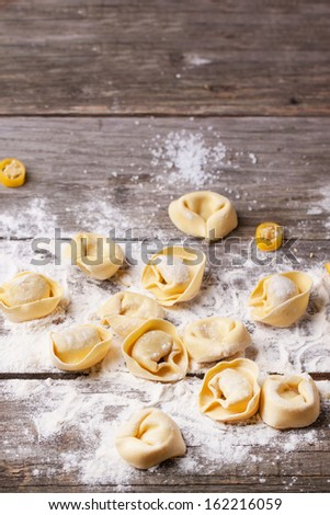 Homemade pasta ravioli over wooden table with flour - stock photo
