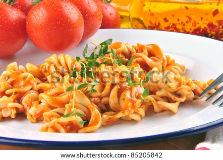 homemade pasta salad on a plate with fresh tomatoes in the background - stock photo