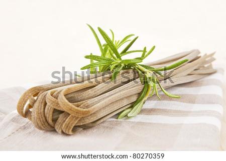 Homemade pasta. Whole grain tagliatelle pasta with fresh rosemary. - stock photo