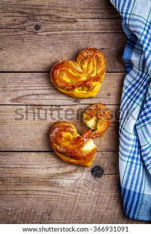 Homemade pastries. Bun heart with kitchen towel on wooden background. Food - stock photo