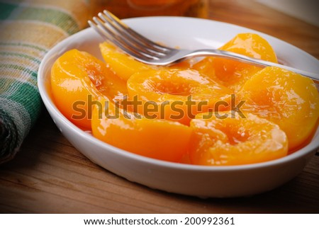 homemade peaches in syrup in white bowl - stock photo