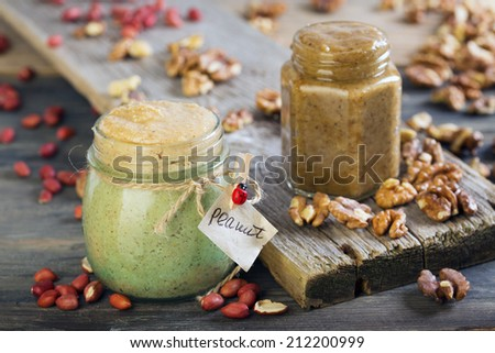 Homemade peanut and walnut butter on a wooden table. - stock photo