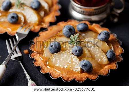 Homemade pear and blueberry tarts on black - stock photo