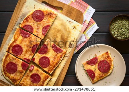 Homemade pepperoni or salami pizza cut in pieces on baking paper on wooden board, photographed overhead on dark wood with natural light - stock photo