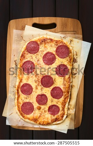 Homemade pepperoni or salami pizza on baking paper on wooden board, photographed overhead on dark wood with natural light - stock photo