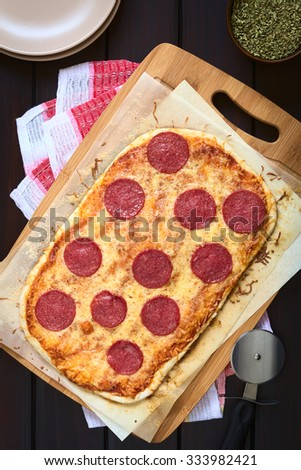 Homemade pepperoni or salami pizza on baking paper on wooden board with plates, dried oregano and pizza cutter on the side, photographed overhead on dark wood with natural light - stock photo
