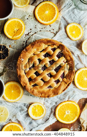 Homemade pesonen cake with cherry filling for breakfast family. Homemade cherry pie on rustic background. Rustic dark styling. Cherry  pie with cut piece on a marble background, overhead scene - stock photo
