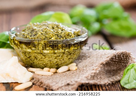 Homemade Pesto Sauce (with ingredients) on dark wooden background - stock photo
