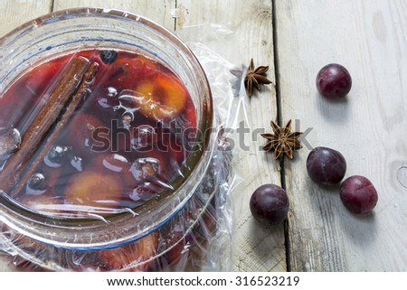Homemade pickled plums with spices in a glass jar on a rustic wooden table - stock photo