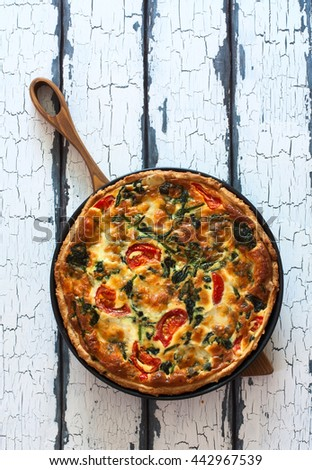 Homemade pie ( quiche) with spinach, tomatoes and soft cheese over grunge wood background