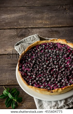 Homemade pie with bilberry decorated by bilberry leaves on dark wooden table.Style rustic. Selective focus. - stock photo