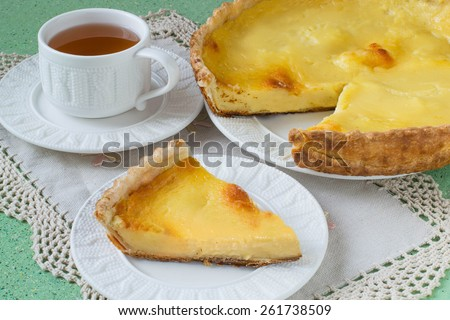 Homemade pie with cheese and custard slice on a plate, cup of tea, a napkin with lace on a green background. Selective focus - stock photo