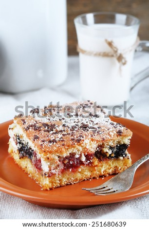 Homemade pie with jam and glass and can of milk on tablecloth and wooden background - stock photo