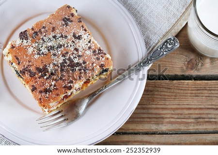 Homemade pie with jam and glass of milk on napkin and wooden planks background - stock photo