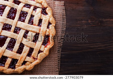 Homemade pie with jam on the wooden table. Top view. Dark toned photo. - stock photo