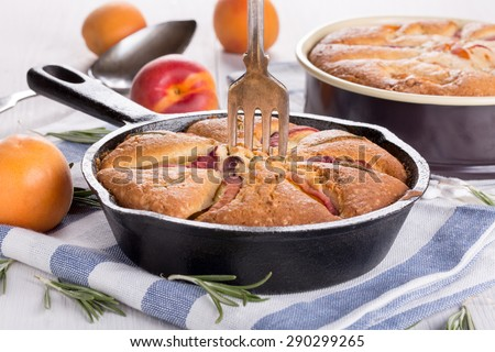 Homemade pie with peaches, apricots and rosemary in a cast iron skillet with a fork stuck upright. - stock photo