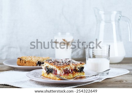 Homemade pies with jam and glass of milk on wooden table and light cloth background - stock photo