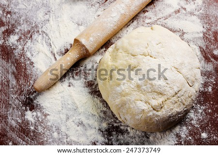 homemade pizza dough with rolling pin on the wooden table - stock photo
