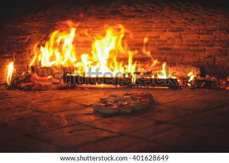 homemade pizza in the simple owen with fire in the backgorund