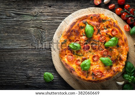 homemade pizza margherita with mozzarella, basil and tomatoes on a wooden board - stock photo