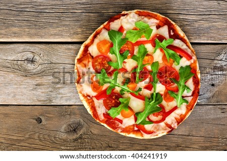 Homemade pizza with arugula and cherry tomatoes against a rustic wood background - stock photo