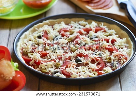 Homemade pizza with pepperoni, pepper and olives. Cooking process. Step 6. Grated cheese added - stock photo