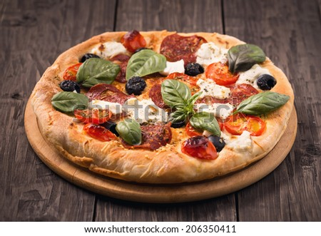 Homemade pizza with salami, mozzarella, olives and basil on rustic wooden surface - stock photo