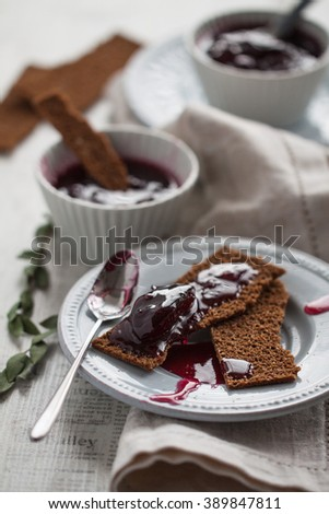Homemade plum and berries jam with rye toasts for the breakfast