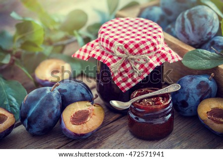 Homemade plum jam and fruits on a wooden table. Retro styled photo.