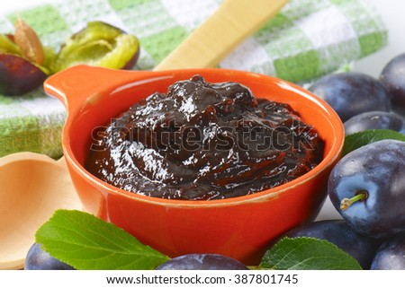 Homemade plum jam in a bowl with fresh fruits on background - stock photo