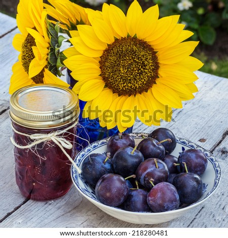 Homemade plum jam with freshly picked plums on wooden table - stock photo