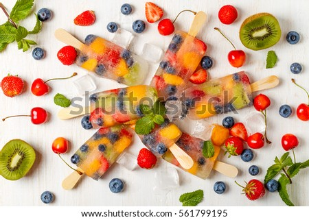 Homemade popsicles with berries and fruits, top view.