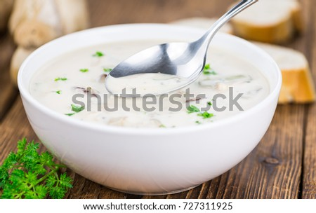 Homemade Porcini Soup on an wooden table as detailed close-up shot; selective focus
