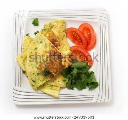 Homemade potato and parmesan cheese frittata omelet, with tomato and rocket, from an Italian recipe, from above - stock photo