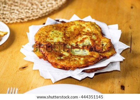Homemade potato pancakes from grated potato with egg, garlic and flour fried until crisp on plate with white napkin on wooden table, food background closeup. European traditional dish.