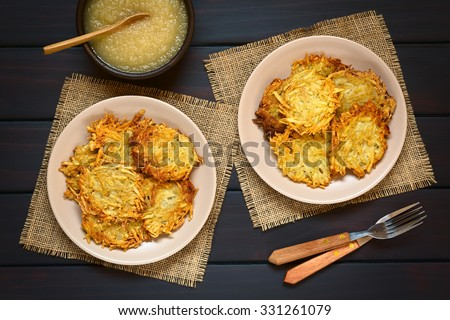 Homemade potato pancakes or fritters on plates with apple sauce, a traditional dish in Germany, photographed overhead on dark wood with natural light