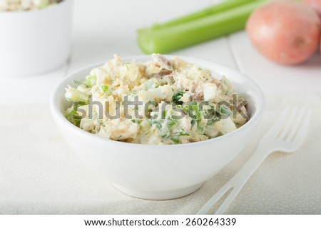 Homemade potato salad Ingredients include celery sticks and herbs in white bowl - stock photo