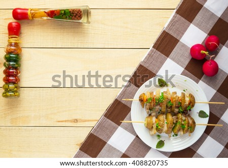Homemade potatoes baked on a thin stick with bacon and herbs on a white plate on a wooden background. The top view. - stock photo