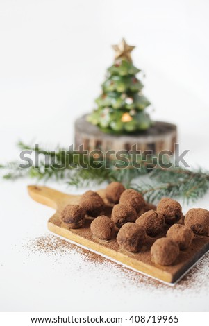 Homemade pralines on a cutting board with Christmas decorations. - stock photo
