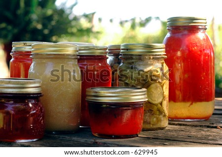 Homemade preserves sitting on a rustic table outside. Pickles, tomatoes, appplesauce, etc. - stock photo