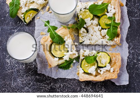 Homemade puff with zucchini and cream cheese on a dark background. Selective focus. - stock photo