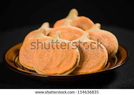 Homemade pumpkin cookies on isolated black background. - stock photo