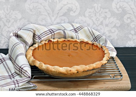 Homemade pumpkin pie, cooling with towel wrap.  Selective focus on front edge of pie.