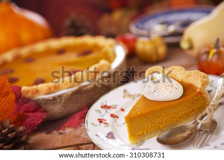 Homemade pumpkin pie on a rustic table with autumn decorations. - stock photo