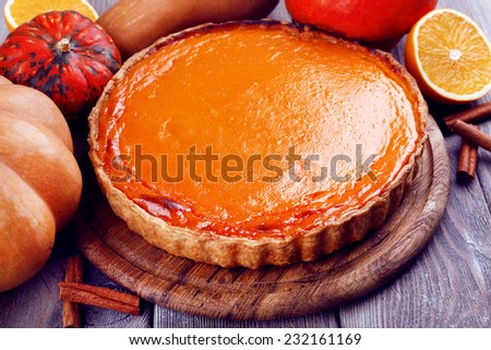 Homemade pumpkin pie on cutting board, on wooden background - stock photo