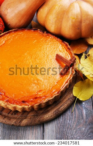 Homemade pumpkin pie on cutting board, on wooden background