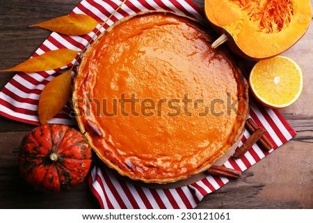 Homemade pumpkin pie on napkin, on wooden background - stock photo