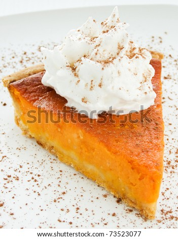 Homemade pumpkin pie with whipped cream. Shallow dof. - stock photo