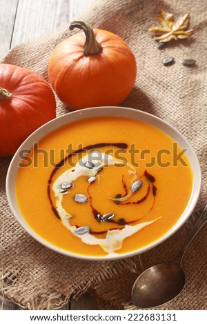 Homemade pumpkin soup for Thanksgiving dinner with fresh ingredients decorated with cream, soy sauce and pumpkin pips for a delicious appetizer - stock photo